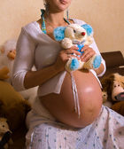 Smiling pregnant woman holding a big toy — Stock Photo