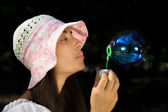 Young girl in the bonnet blowing bubbles — Stock Photo