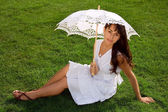 Attractive young girl sitting on the lawn — Stockfoto