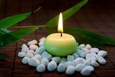 Hořící svíčka s kameny — Stock fotografie