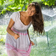 Beautiful girl on the lawn with sprinklers — Stock Photo