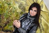 Stijlvolle jong meisje met groene paraplu — Stockfoto