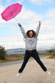 Jumping happy lady with umbrella — Stok fotoğraf