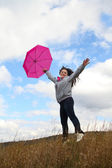 Jumping happy lady with pink umbrella — Stok fotoğraf