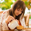 Young woman drinking tea in a cafe outdoors — Stock Photo