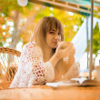 Young woman drinking tea in a cafe outdoors — Stock Photo #4086928