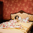 Stock Photo: Pregnant woman resting in her bed in the bedroom at home