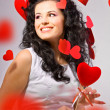 Attractive smiling woman with hearts on white background — Stock Photo