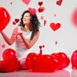 Woman with red heart balloon on a white background — Стоковая фотография