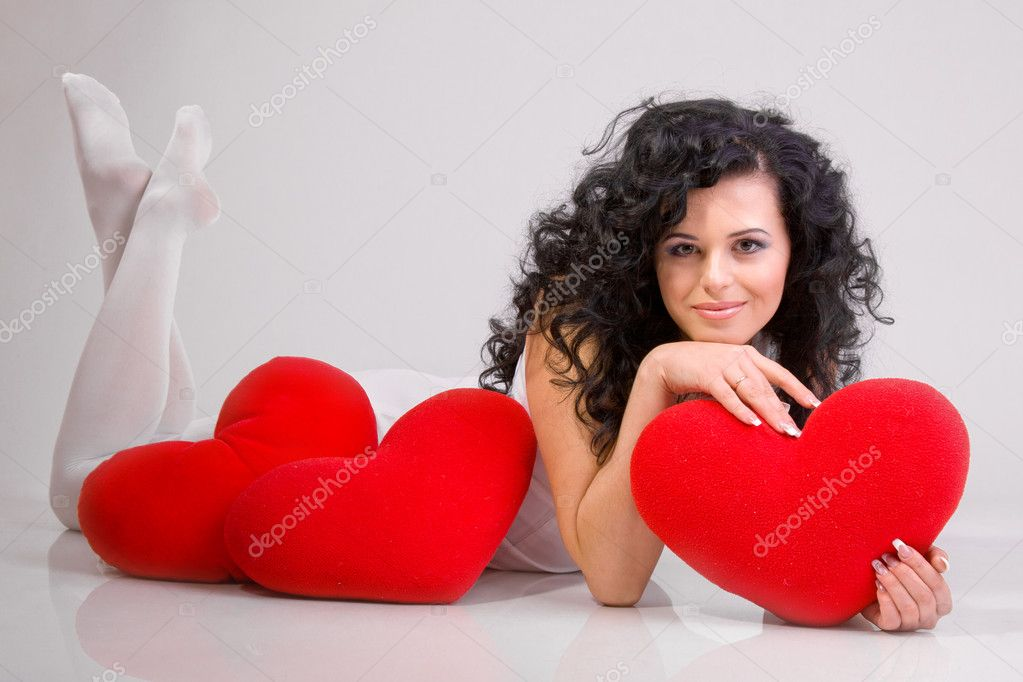 Romantic concept with girl and heart-shaped pillows — Stock Photo #4675124