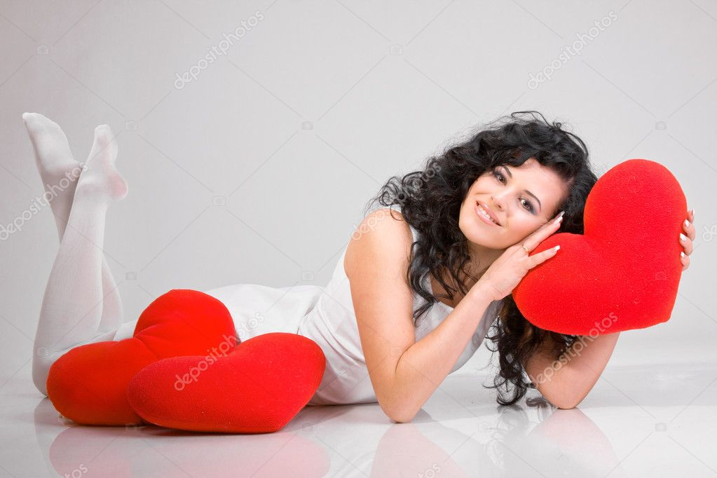 Romantic concept with girl and heart-shaped pillows — Stock Photo #4675130