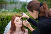 Young beautiful bride applying wedding make-up by professional make-up arti — Stock Photo