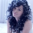 Стоковое фото: Smiling young woman with feathers on a bed