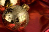 Gold baubles with red backdrop — Stock Photo
