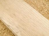 Board on sawdust — Stock Photo