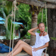 Woman relaxing on swing at a tropical beach — Stock Photo #4258283