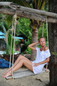 Woman relaxing on swing at a tropical beach — Stock Photo