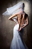 Lovely sensual bride unzip her wedding dress — Stock fotografie