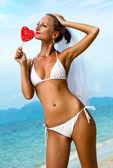 Beautiful bride holding a lollipop on the beach — Stock Photo