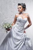 Beautiful bride holding wedding bouquet — Stock Photo