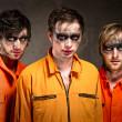 Three criminals in orange uniforms indoors — Stock Photo