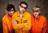 Three guys in orange uniforms indoors — Stock Photo