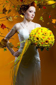 Beautiful redhead bride with a bouquet of flowers — Stock Photo