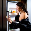 Stock Photo: Womlooking for something to eat inside fridge