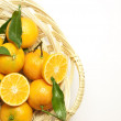Fresh mandarines with green leaves in a pad — Stock Photo