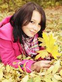 Girl on the foliage — Stock Photo