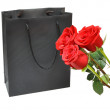 Black gift bag with red roses — Stock Photo