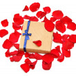 Red rose petals and gift — Stock Photo