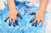 Child hands painted in blue paint — Stok fotoğraf