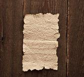 Old paper on brown wood texture — ストック写真