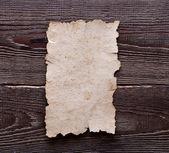 Oud papier op bruin houtstructuur — Stockfoto