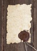 Vieux papier avec un sceau de cire sur la texture du bois brun — Photo