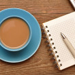 Coffee cup, spiral notebook and pen on the old wooden table — Stockfoto