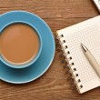 Coffee cup, spiral notebook and pen on the old wooden table — Stok fotoğraf