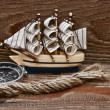 Royalty-Free Stock Photo: Compass, rope and model classic boat on wood background