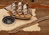 Old paper, rope and model classic boat on wood background — Stock Photo