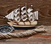 Compass, rope and model classic boat on wood background — Stock Photo