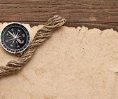 Vecchia carta, bussola e corda su sfondo legno — Foto Stock