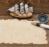 Old paper, compass, and model classic boat on wood background — Stock Photo