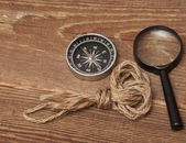 Rope, compass and magnifying glass on wood background — Stock Photo
