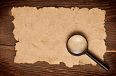 Magnifying glass on old paper — Stockfoto