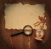 Old paper with pocket watch and magnifying glass — Stock Photo