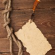Old paper pinned to a wooden wall with a knife — Stock Photo