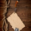 Stock Photo: Old paper pinned to a wooden wall with a knife