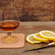 Classic cognac with lemon and knife — Stock Photo #4872033