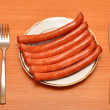 Royalty-Free Stock Photo: A fresh sausage on white plate with fork and knife